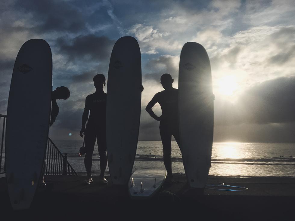サーフボードと朝日をバックに記念撮影