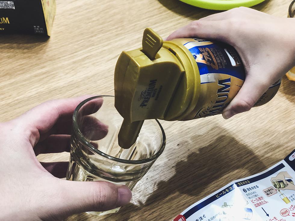 缶ビールの泡がクリーミーになる神泡サーバーを装着したプレモルをコップにそそぐ