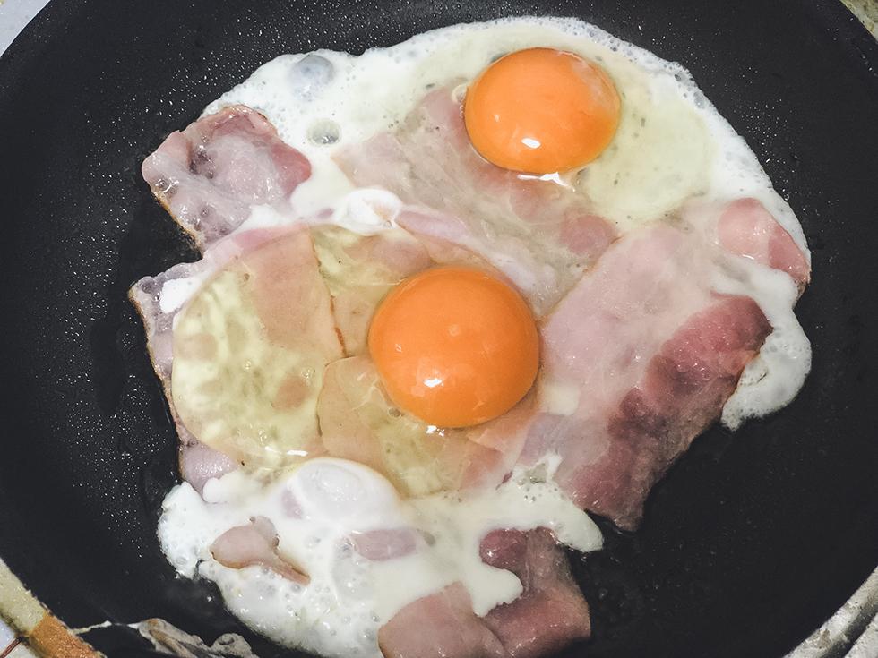 フライパンで焼いているベーコンの上に卵をのせて焼く