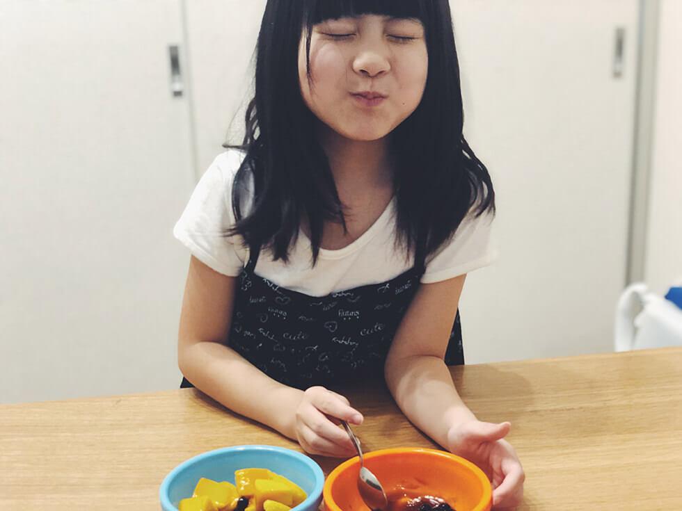作った冷凍タピオカと冷凍アップルマンゴーのデザートを子どもが食べているところ