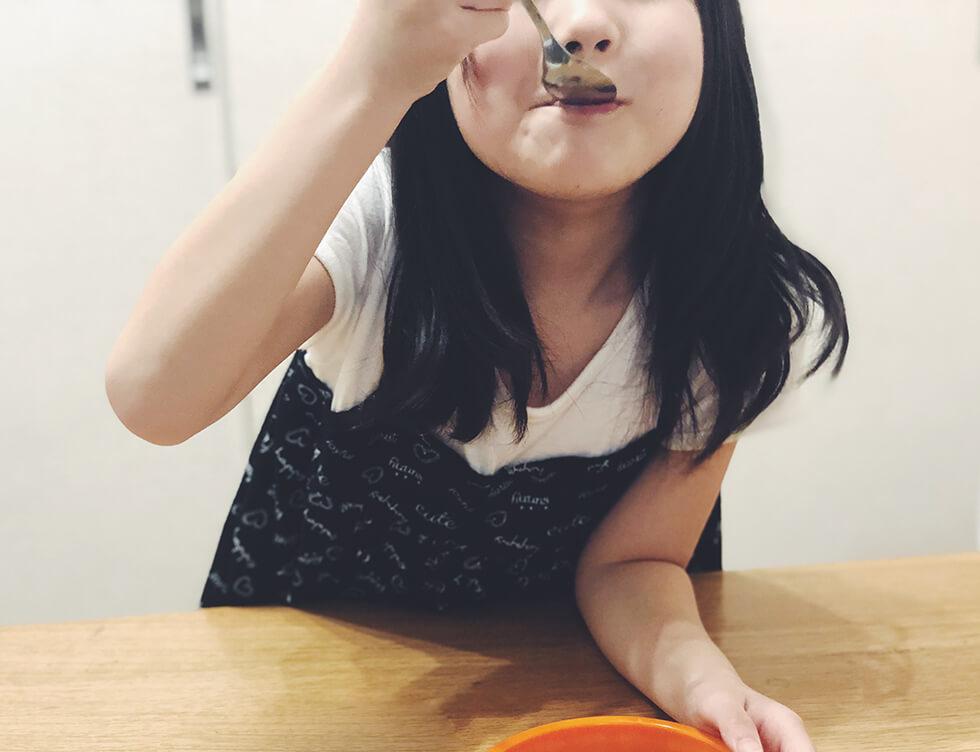 黒蜜シロップをかけたタピオカデザートを食べている子供