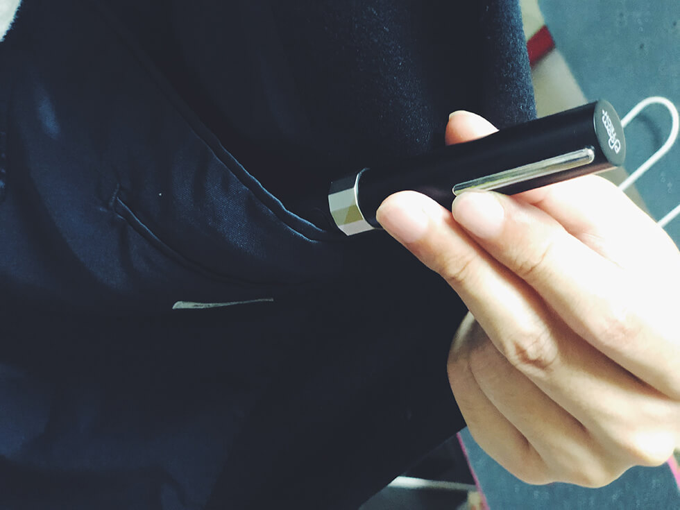 スーツのポケットにメタルキャップを付けたプルームテックプラスを入れているところ