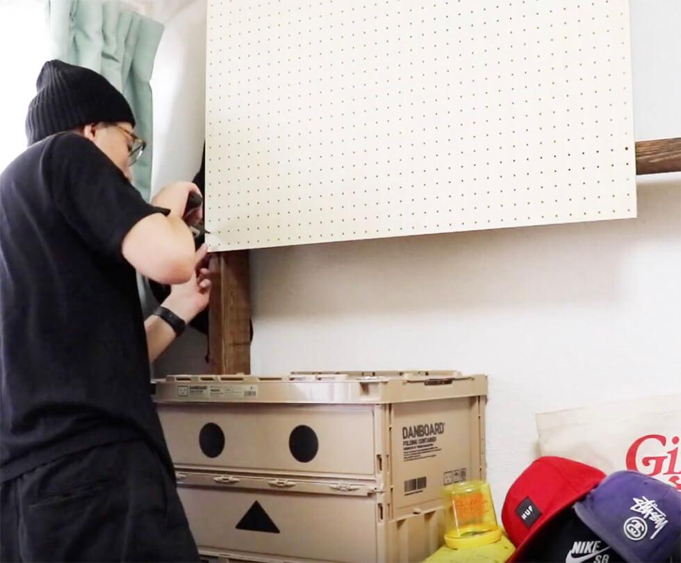 有孔ボードを壁面棚に取り付けているところ